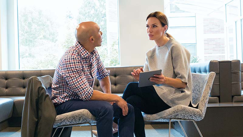 A man and a woman talking in an office